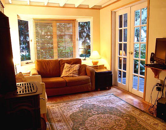 The living room of the Gingerbread cottage in Point Roberts surrounds you in visions of cedars and ferns through antique windows.
